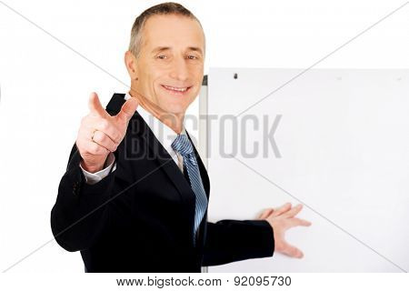 Mature businessman with marker pointing on someone.