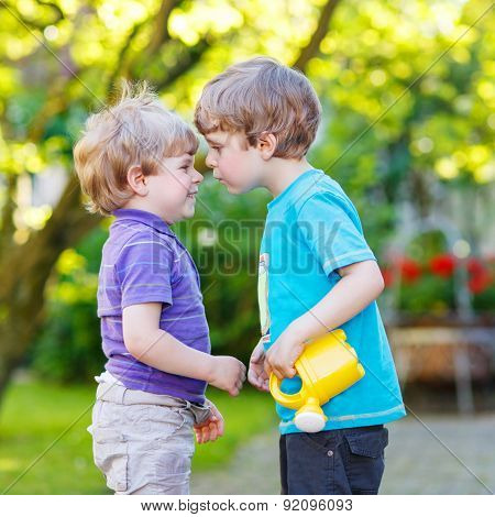 Two Little Sibling Boys Hugging And Having Fun Outdoors