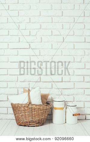 basket with a pillow and milk cans