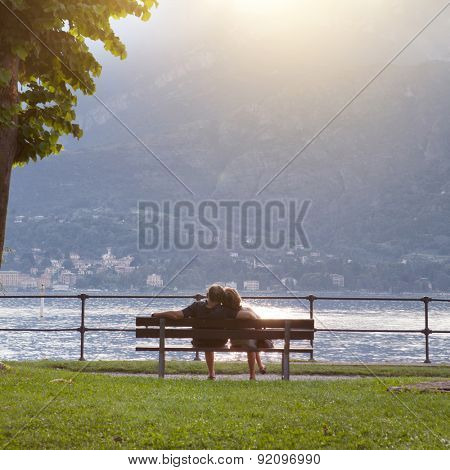 Couple sitting on the bench and looking at beautiful view of Como lake on sunset in Bellagio, Italy