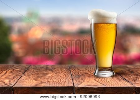 Glass of beer on wooden table with summer in Prague on background. Natural bokeh