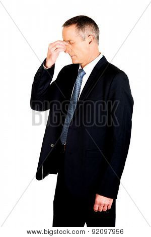 Mature businessman suffering from sinus pain.