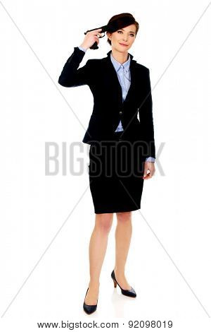 Despair businesswoman holding a gun near head.
