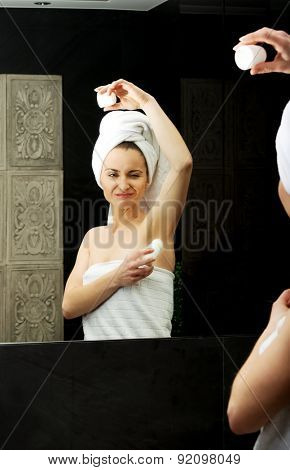 Woman using deodorant in the bathroom.