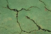 foto of netball  - Close up view of a cracked tennis court surface in need of repair - JPG