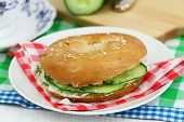 image of bagel  - Bagel with cream cheese and cucumber on checkered napkin - JPG