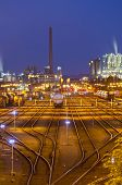foto of railroad yard  - An illuminated railroad yard with trains and other industry in the background at night - JPG