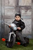 picture of tricycle  - Adorable toddler wearing a skull and crossbones scarf and leather jacket and riding a toy tricycle - JPG