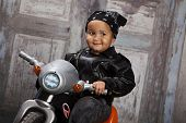 picture of tricycle  - Adorable mixed race toddler wearing a bandanna and leather jacket and riding a toy tricycle - JPG