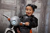 foto of tricycle  - Adorable mixed race toddler wearing a bandanna and leather jacket and riding a toy tricycle - JPG