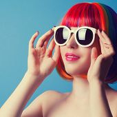 stock photo of wig  - beautiful woman wearing colorful wig and white sunglasses against blue background - JPG