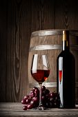 stock photo of keg  - Glass of red wine with bottle and keg standing on a wooden background - JPG