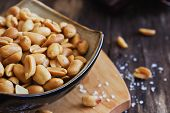 picture of salt-bowl  - salted peanut nuts in a bowl on the old wooden background. snacks. close-up. selective focus ** Note: Shallow depth of field - JPG