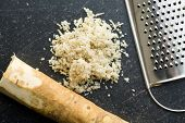foto of grated radish  - grated horseradish root on kitchen table - JPG