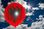 stock photo of albania  - balloon in colors of albania flag flying on blue sky