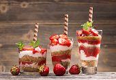stock photo of yogurt  - Fresh strawberry yogurt parfait on wooden background - JPG