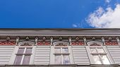 pic of tenement  - Facade of an ancient tenement with sunbeams reflecting in a window pane in Bielsko - JPG