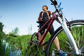 foto of swamps  -  Young man with dirty clothes standing with his bicycle in the swamp - JPG