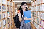pic of indian apple  - Female high school student standing in the library while holding an apple fruit and folder - JPG