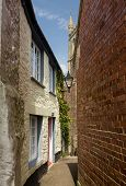 stock photo of church-of-england  - Traditional narrow path or alley leading past old houses to the parish church in Fowey Cornwall England UK - JPG