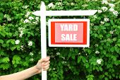 pic of yard sale  - Wooden Yard Sale sign in female hand over green bush and flowers background - JPG