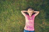 image of beautiful senior woman  - Beautiful senior woman lying on a grass in a park - JPG
