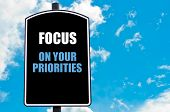 image of priorities  - FOCUS ON YOUR PRIORITIES motivational quote written on road sign isolated over clear blue sky background with available copy space - JPG