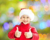 image of santa claus hat  - little girl in a Santa Claus hat shows two thumbs on a colorful background - JPG