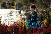 stock photo of beside  - Princess beside a stream with a dove in her hands - JPG
