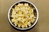 pic of paneer  - Sliced fresh cheese or paneer kept on a vessel on a plain background - JPG