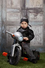 picture of skull crossbones  - Adorable toddler wearing a skull and crossbones scarf and leather jacket and riding a toy tricycle - JPG