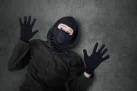 foto of shoplifting  - Closeup of male thief with balaclava looking at the camera with fear expression after caught - JPG