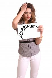 picture of horrifying  - Young attractive woman holding paper with Horrified text on white background - JPG