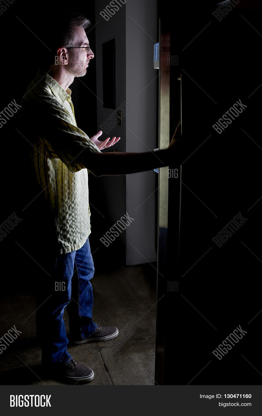 Dark Kitchen At Night man looking for food in an open fridge in a dark kitchen late at