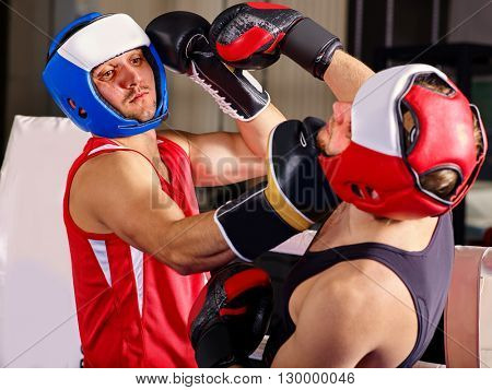 Two  men boxer wearing helmet and  gloves boxing. Boxing is  extreme sport.