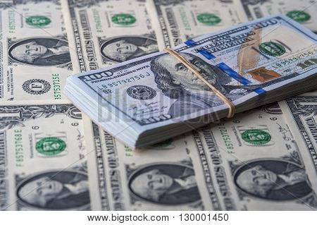 Stack of one hundred dollar bills on money background