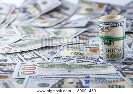 Dollar roll on the background of one hundred dollar bills