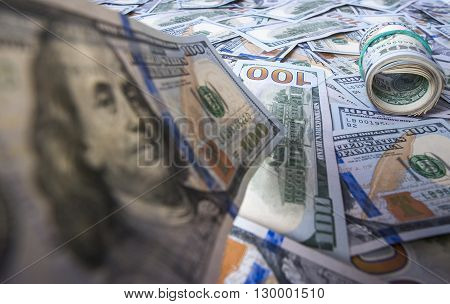 One hundred dollar bill on the background of dollar heap