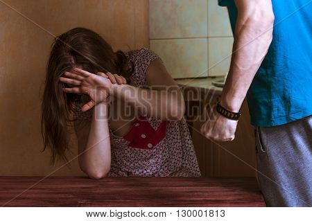 Woman covering her face in fear of domestic violence. Aggression in the family.