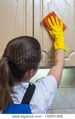 Female janitor in yellow gloves wiping kitchen cupboard with rag