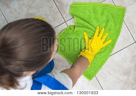 Female cleaner with green rag washing floors. Selective focus.