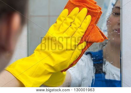 Woman cleaning mirror with rag at home. Cleaning and housework concept.