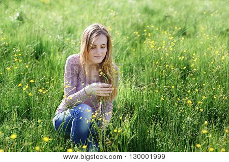 young woman picking flowers on a summer meadow.