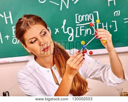 Chemistry female teacher with test-tube at classroom. Chemistry teacher in class alone.