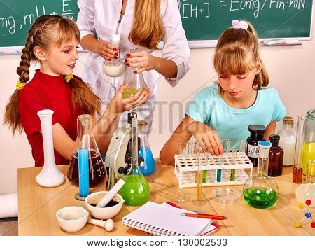 Teacher with children holding flask in chemistry class. Chemistry experiment.
