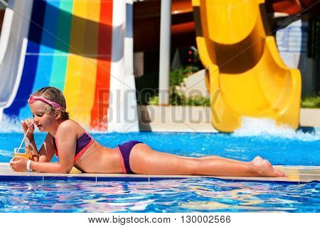 Child on water slide at aquapark are drinking cold drinks. Child lie on edge of swimming pool. Child activities lifestyle. Summer holiday. Outdoor.