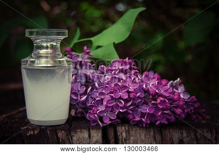 Perfume Bottle With A Sprig Of Lilac On A Wooden Background