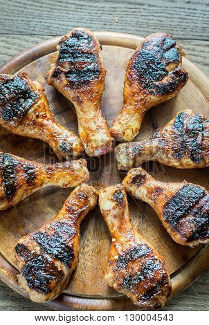 Grilled chicken drumsticks on the wooden board