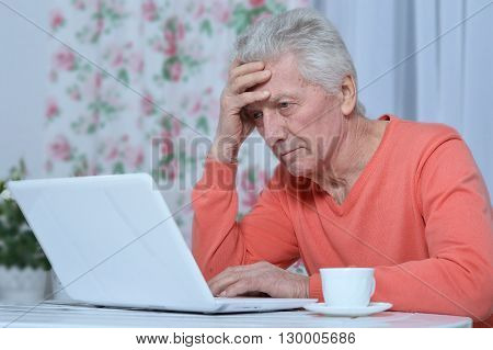Portrait of  senior man  in the kitchen at home with laptop