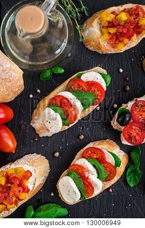 Italian bruschetta with tomatoes, mozzarella cheese and herbs